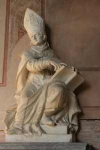"""A statue of a bishop or cardinal or pope strikes a particularly effeminate pose as he gazes at the sculptor while holding an open book"".  Image by Holoweb"